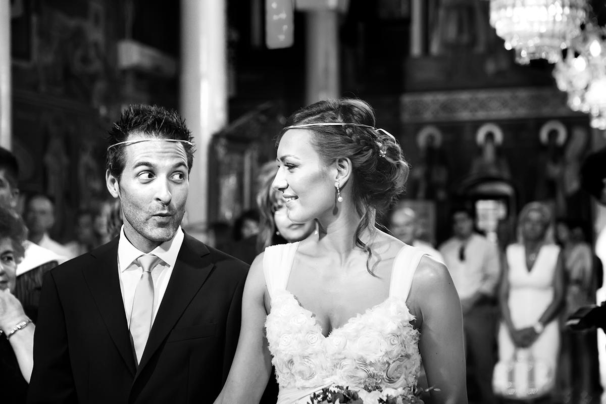 η φωτογράφηση γάμου της Αλεξάνδρας και του Alex ,γαμπρός κοιτάει τη νύμφη  και οι δύο φοράνε τα στέφανα