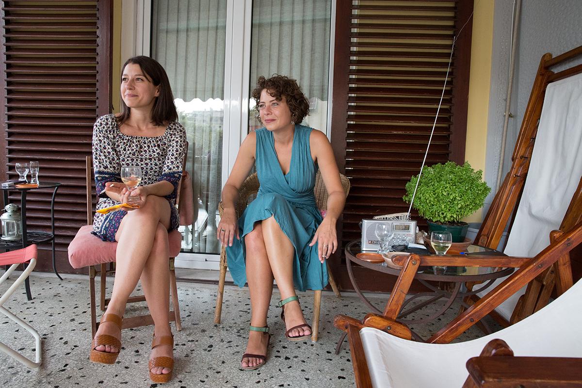 η φωτογράφιση γάμου της Δέσποινας και του Νίκου ,φίλες της νύφης κάθονται στο μπαλκόνι .φωτογράφος γάμου από τη θεσσαλονίκη.