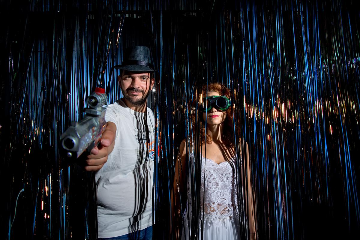 η φωτογράφιση γάμου της Δέσποινας και του Νίκου,στουντιακή φωτογράφιση γάμου ,γαμπρός σημαδεύει με παιδικό όπλο το  φωτογραφικό φακό