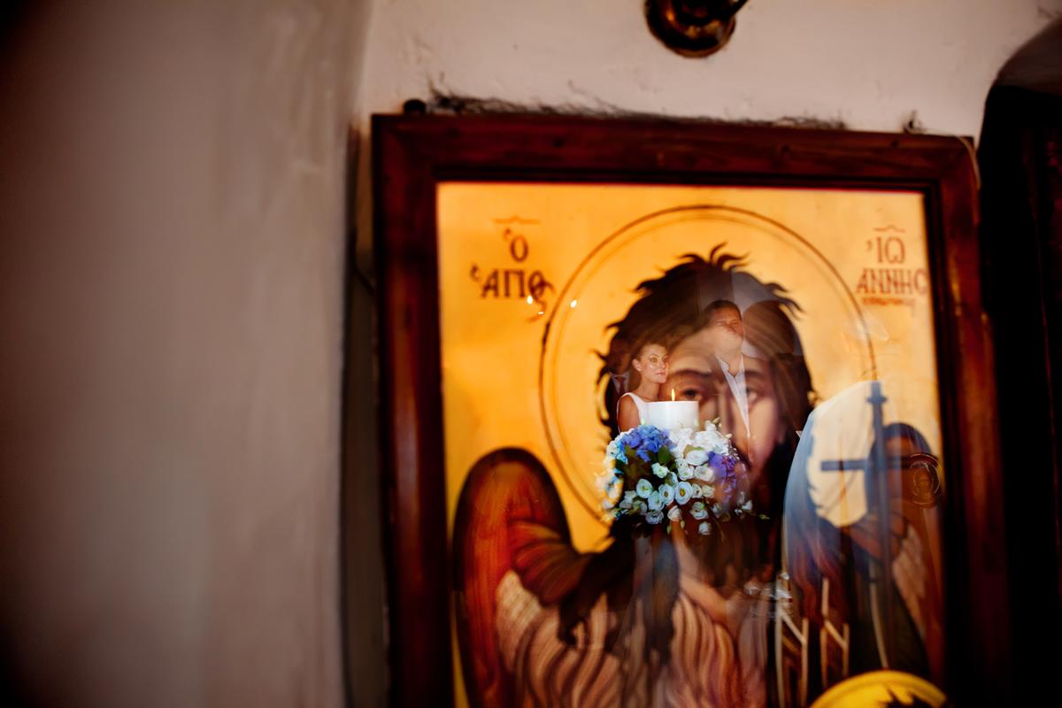 φωτογράφηση γάμου στη Λευκάδα ,το ζευγάρι αντικατροπτίζεται μέσα στην εικόνα του Χριστού.
