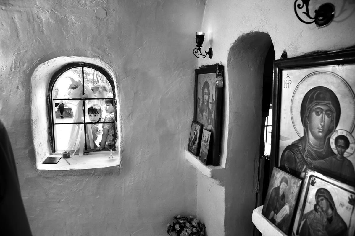 φωτογράφηση γάμου στη Λευκάδα ,δυο παιδιά κοιτάν από το παραθύρι της εκκλησίας,στα δεξιά της φωτογραφίας γάμου φαίνεται η εικόνα της Παναγίας.