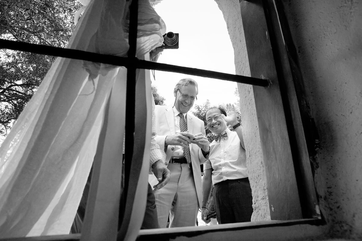 φωτογράφηση γάμου στη Λευκάδα ,δύο καλεσμένοι χαμογελαστοί χαιρετούν το φωτογράφο γάμου.