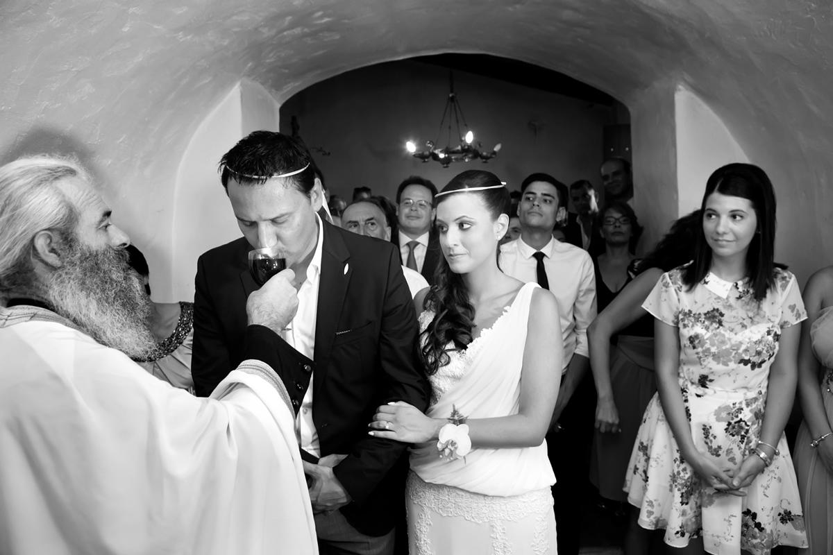 φωτογράφηση γάμου στη Λευκάδα,ο γαμπρός πίνει το κρασί,η νύφη του πιάνει ευγενικά το μπράτσο, η κουμπαρα κοιτά με χαρά