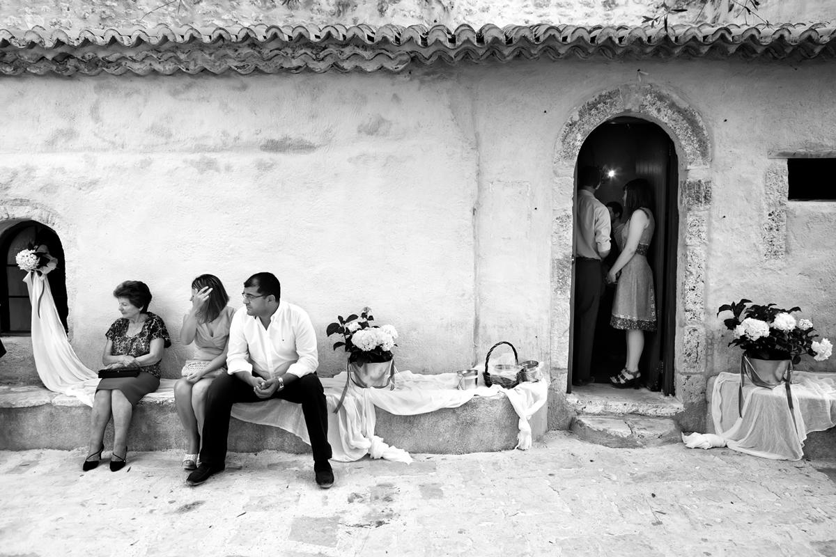 φωτογράφηση γάμου στη Λευκάδακαλεσμένοι του γάμου κάθονται στο πεζούλι της αυλής.στην είσοδο της εκκλησίας βρίσκεται μια κοπέλα