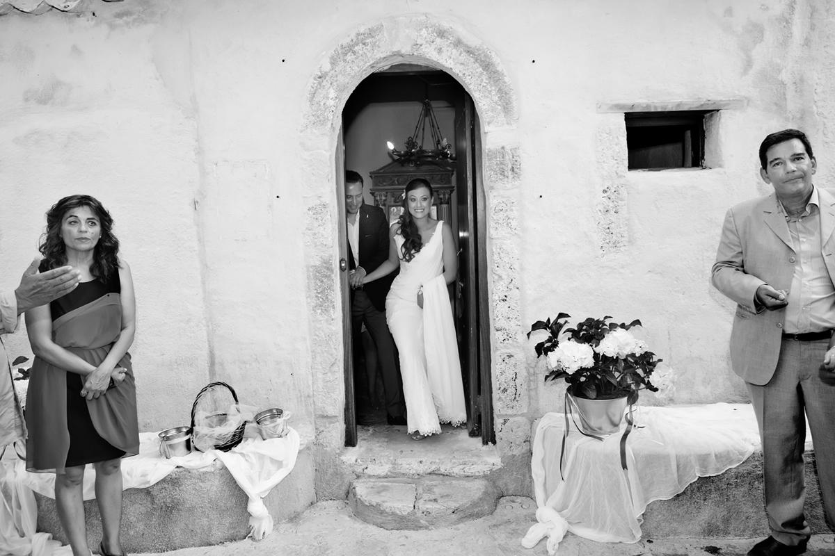 φωτογράφηση γάμου στη Λευκάδα,το νεόνυμφο ζευγάρι ξεπροβάλλει στην είσοδο της εκκλησίας.