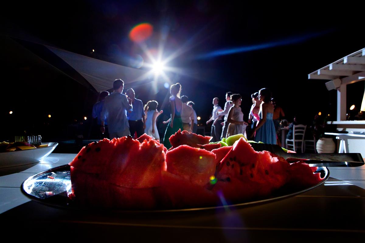 φωτογράφηση γάμου στη Λευκάδα,φωτογραφία γάμου από τη δεξίωση.καρπούζι.σε πρώτο πλάνο ,στο δεύτερο χορεύουν οι καλεσμένοι