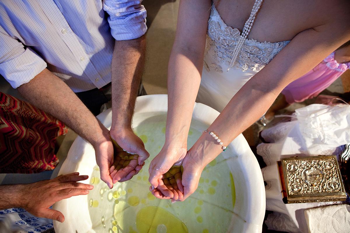 φωτογράφηση βάπτισης στο Πανόραμα της Θεσσαλονίκης .τα χέρια των νονών γεμάτο λάδι, φωτογράφος γάμου από Θεσσαλονίκη.