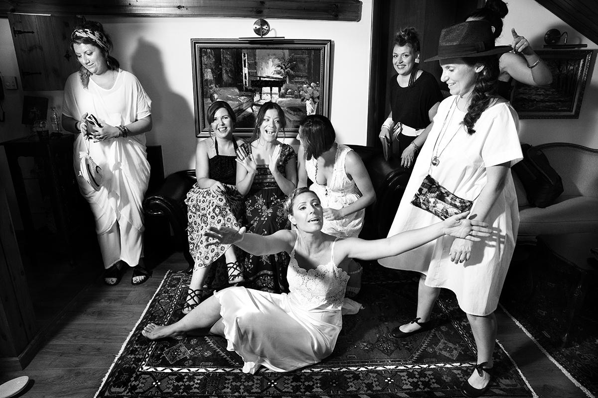 Η ξεχωριστή φωτογράφηση γάμου του Νικου και της Μαριας.η νύφη με ανοικτά χέρια .η νύφη κάθεται στο χαλί δίπλα σε φίλους.