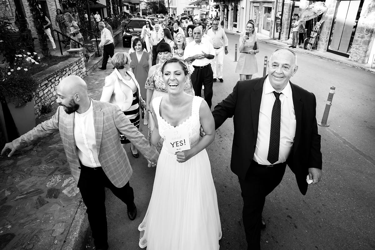 Η ξεχωριστή φωτογράφηση γάμου του Νικου και της Μαρια.η νύφη χαρούμενη βαδίζει προσ την εκκλησία.ο αδελφός και ο πατέρας της την κρατούν από το μπράτσο.ς