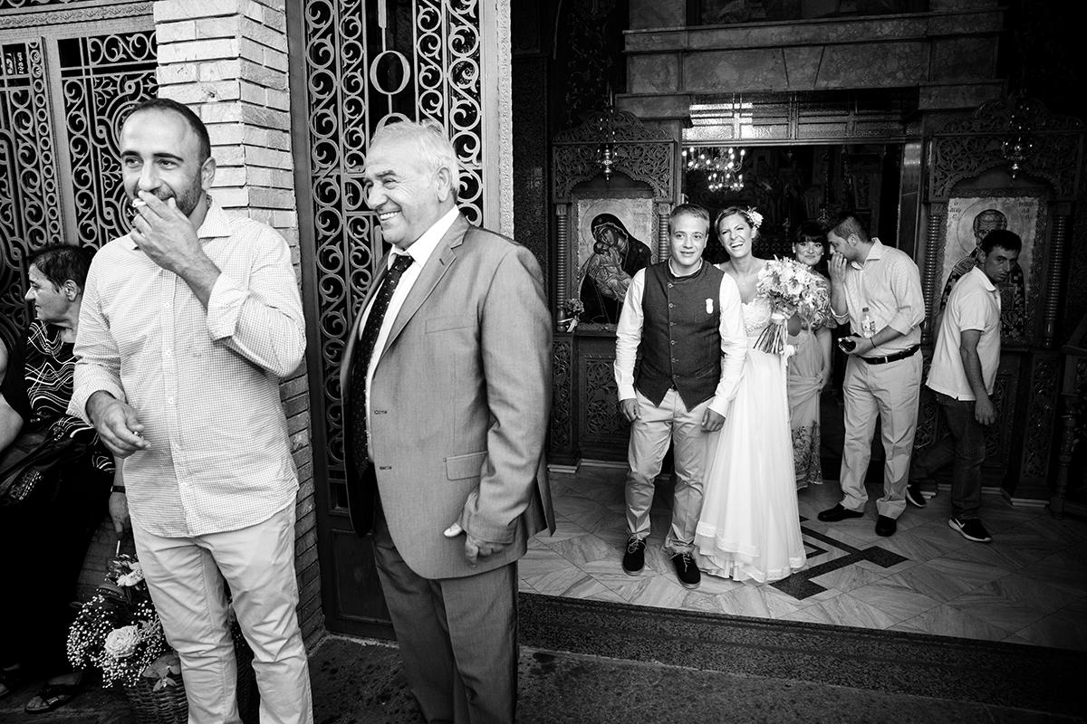 Η ξεχωριστή φωτογράφηση γάμου του Νικου και της Μαρια.πατέρας και αδελφός χαμογελούν ενώ οι νεόνυμφοι ξεπροβάλλουν . πολύ όμορφη στιγμή του γάμους