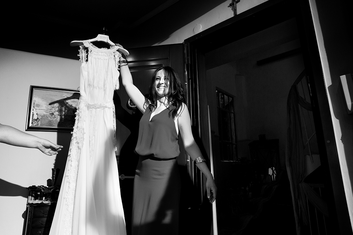 η κουμπάρα φέρνει το νυφικό.φωτογράφιση γάμου σε ασπρόμαυρο φόντο.φωτογραφία γάμου.Ο γάμος της Ροζμαρί και του Μάκη