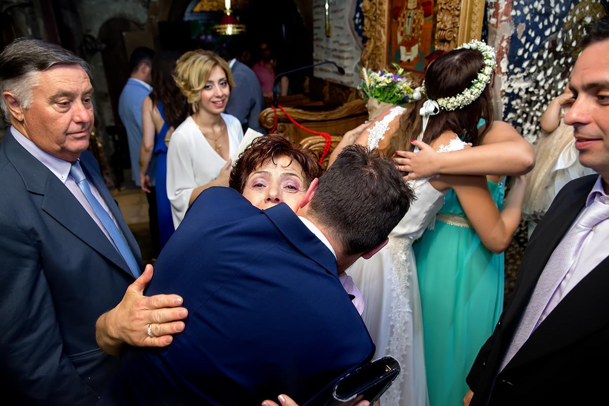 φωτογραφία γάμου.Ο γάμος της Ροζμαρί και του Μάκη.η μητέρα του γαμπρού τον αγγαλιάζει.φωτογραφία γάμου στη θεσσαλονίκη στη μονή Βλατάδων.