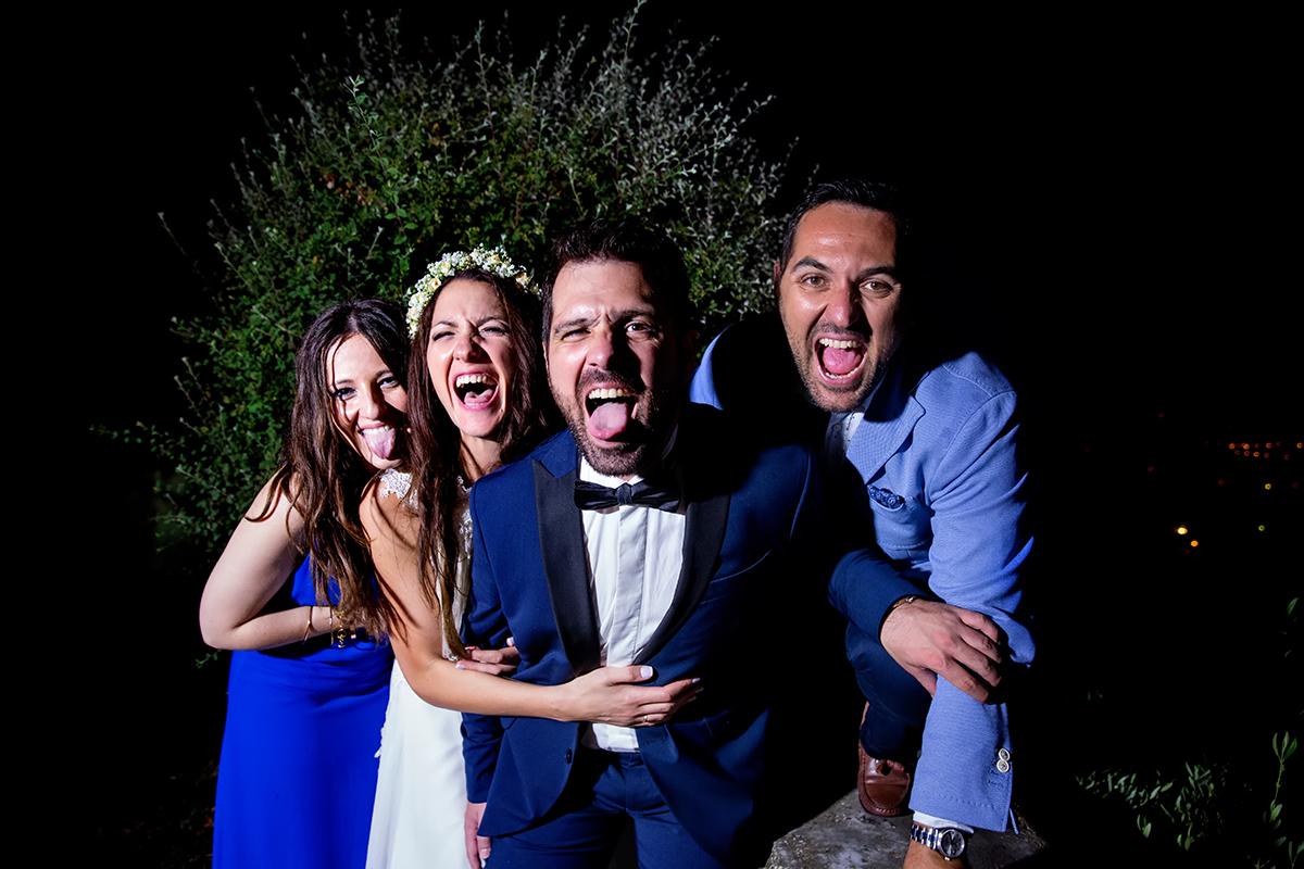 φωτογραφία γάμου.Ο γάμος της Ροζμαρί και του Μάκη.το ζευγάρι και οι κουμπάροι βγάζουν τη γλώσσα τους στο φωτογραφικό φακό.φωτογράφιση γάμου στη θεσσαλονίκη
