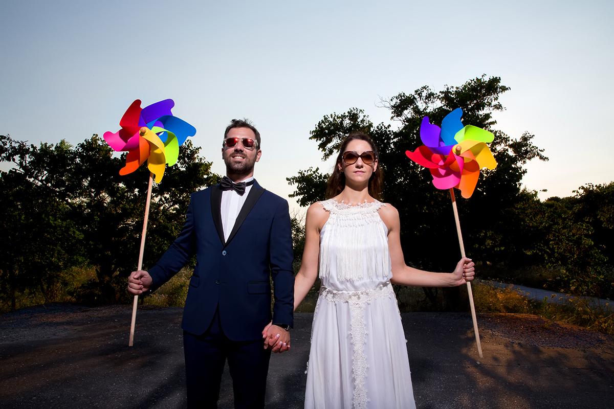 φωτογραφία γάμου.Ο γάμος της Ροζμαρί και του Μάκη.φωτογράφος γάμου από τη θεσσαλονίκη.το νεόνυμφο ζευγάρι κρατάει παιδικά φουρφούρια. γυαλιά ηλίου