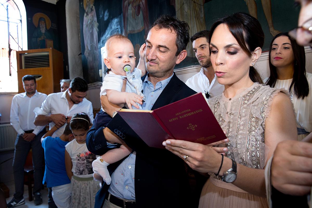 φωτογράφιση βάπτισης. Οι νονοί διαβάζουν το πιστεύω