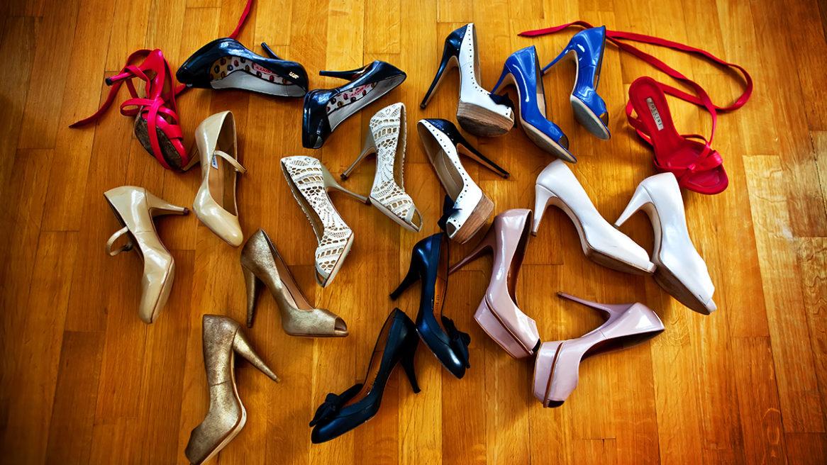 πολλά παπούτσια τοποθετημένα γύρω από τα νυφιάτικα παπούτσια στο ξύλινο πάτωμα του σαλονιού.