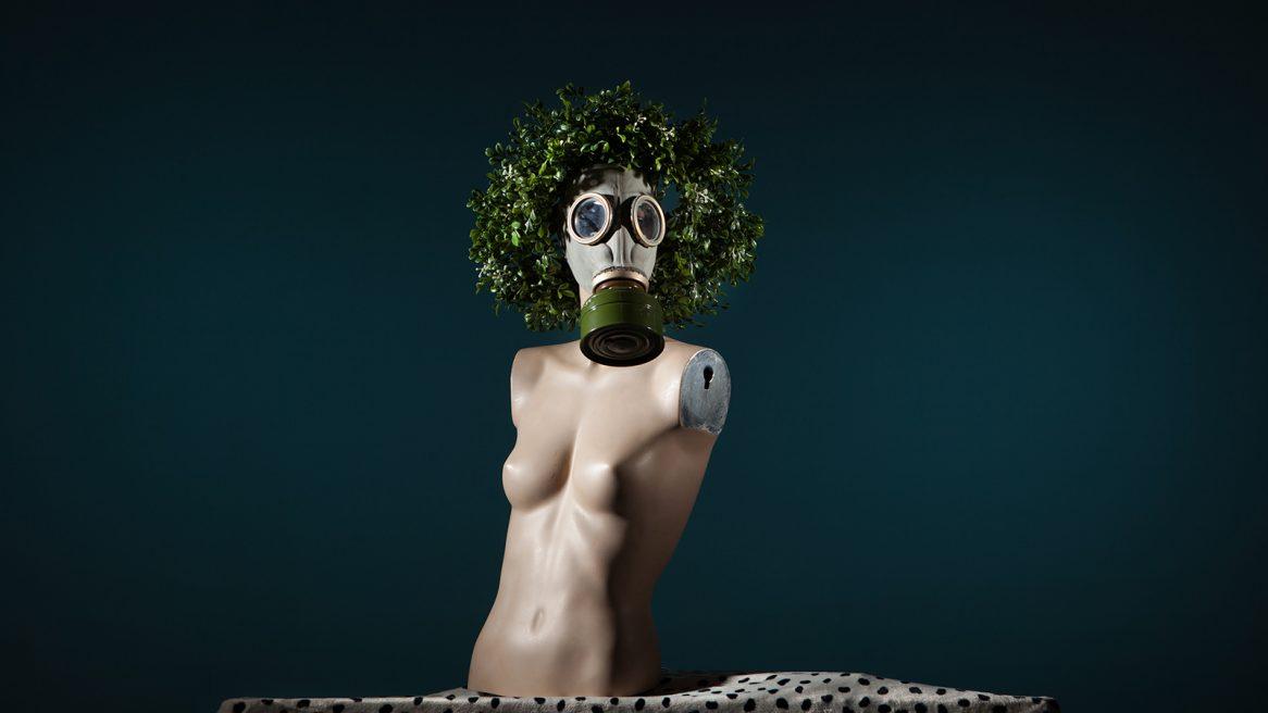 κούκλα φοράει μάσκα χημικού πολέμου, φοράει επίσης στεφάνι από ψεύτικα λουλούδια