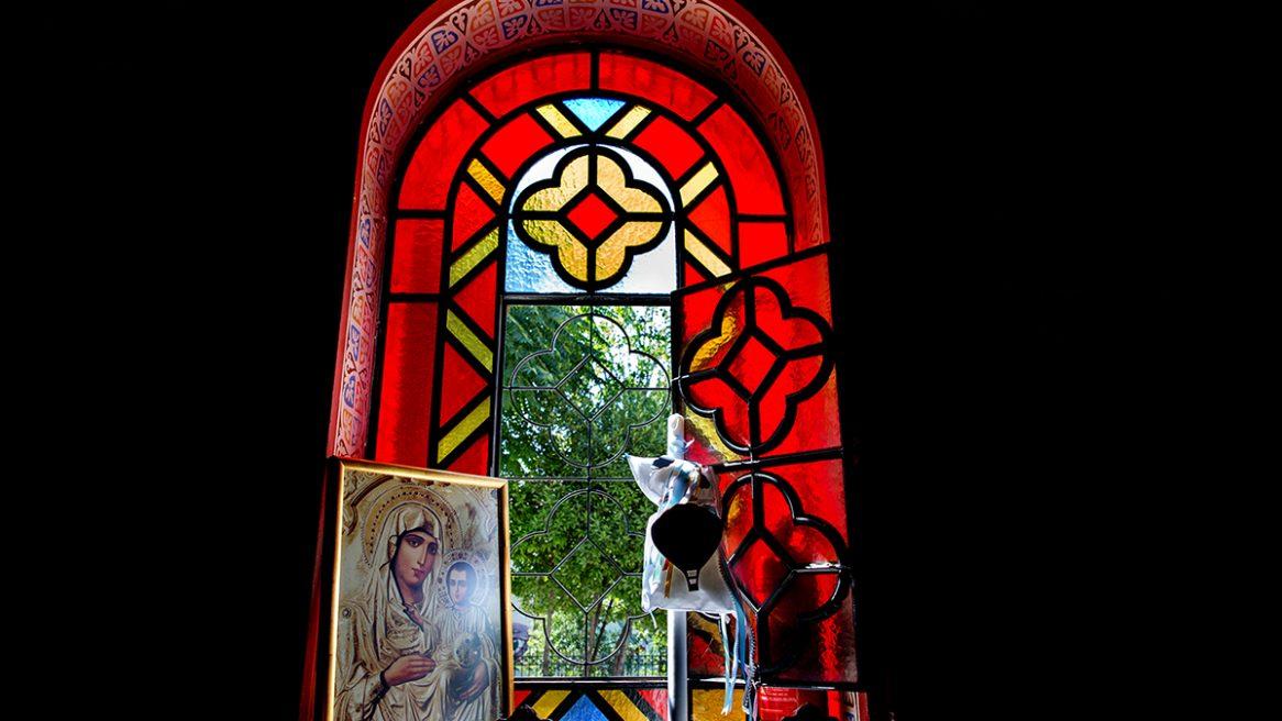 το παράθυρο της εκκλησίας , κόκκινο βιτρό. εικόνα της Παναγίας.