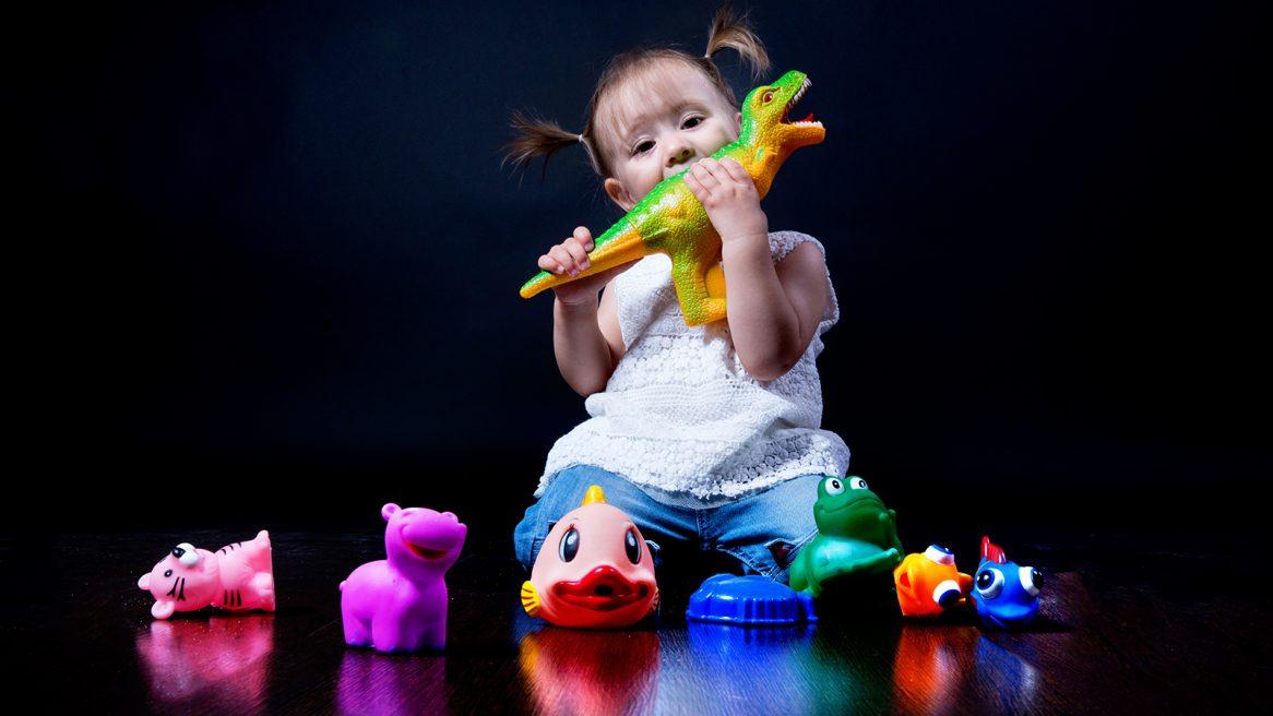 φωτογράφηση στο στούντιο. Η μικρή τρώει έναν πολύχρωμο, πλαστικό δεινόσαυρο.