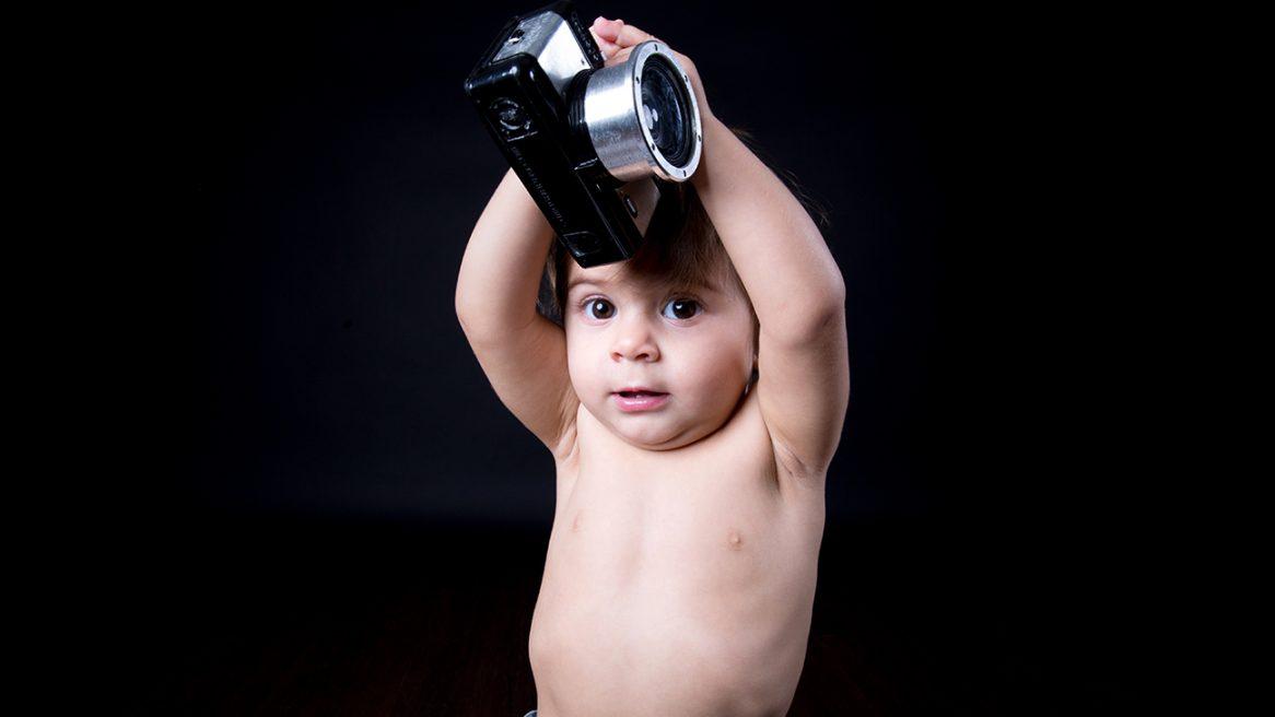 η μικρά σηκώνει πάνω από το κεφάλη της μια παιδική φωτογραφική μηχανή. Την πιάνει με τα δυο της χάρια.