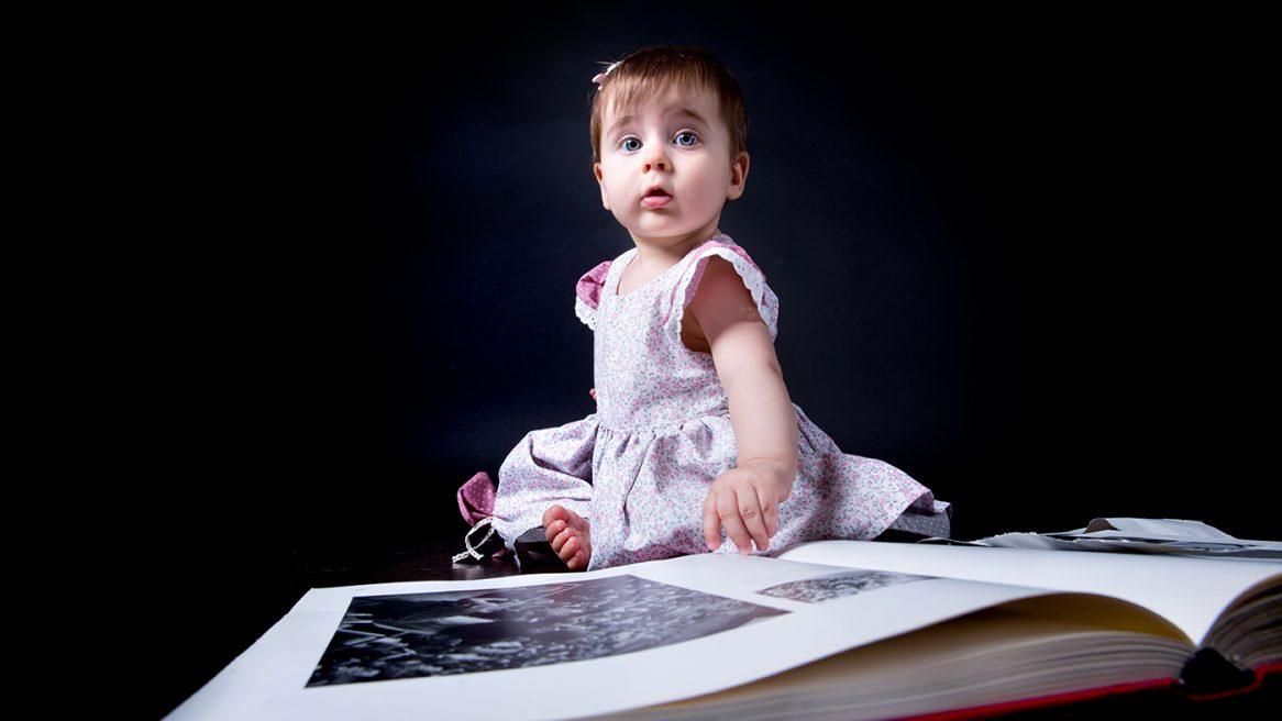 φωτογραφία στο στούντιο της μικρής Ευαγγελίας. Η μικρή Ευαγγελία ακουμπάει ένα βιβλίο που είναι μπροστά της.